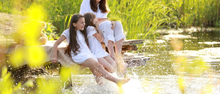 Pension mother and daughter relaxing in the sun, splashing feet in a lake - comprehensive financial planning
