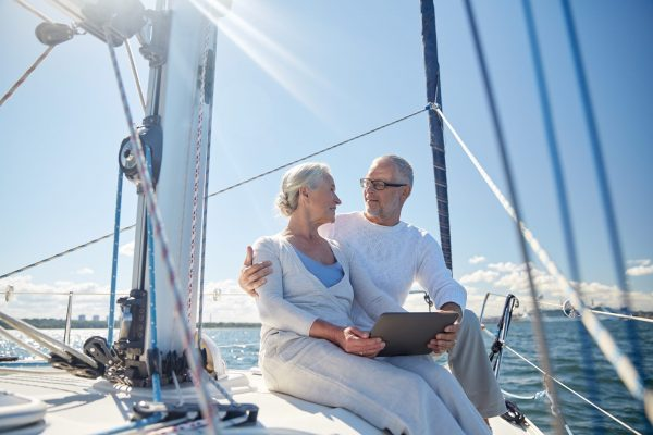 rich couple sitting in a sailing yacht with tablet